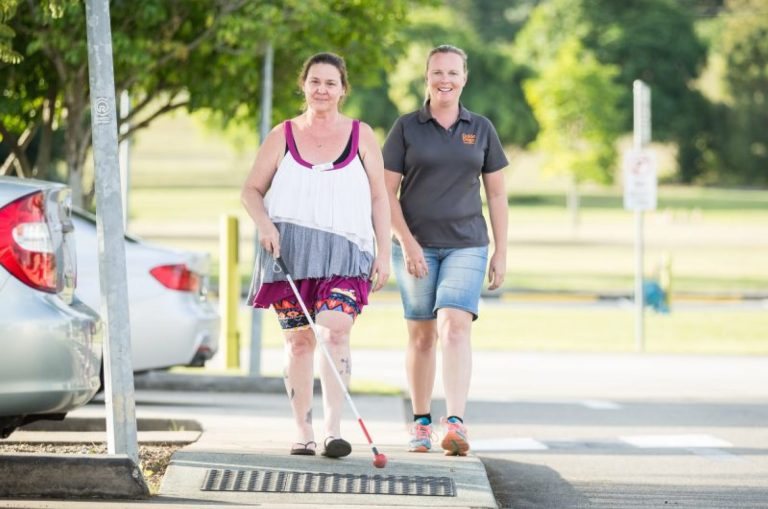 A person crossing the road with their white cane while a Guide Dog's staff member walks beside them. They are both looking at the camera smiling.