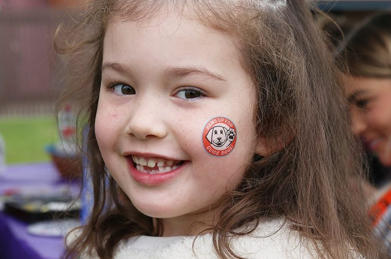 A young child with face paint on its face is smiling at the camera.