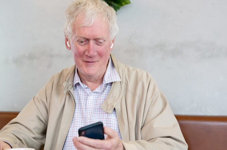 An older adult man sitting at a cafe looking at their phone.