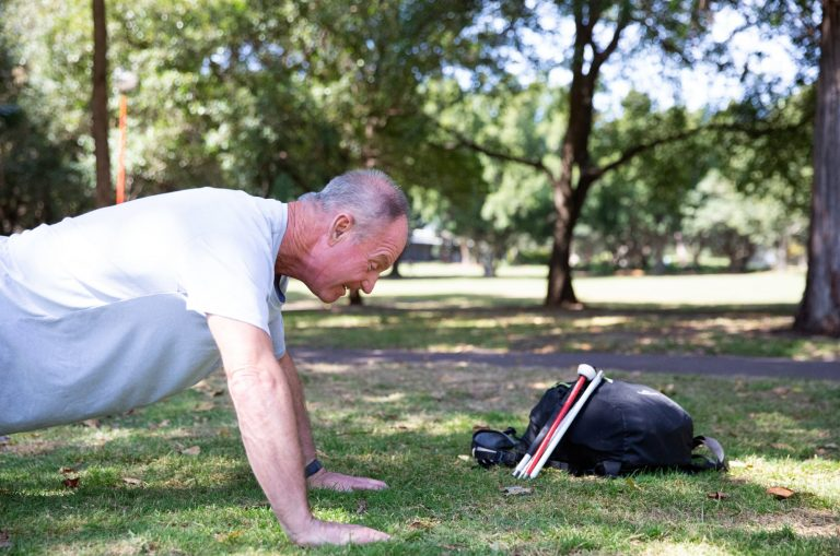 A person doing push ups outside in the park. There is a black bag near them with a folded white cane leaning up against the bag.
